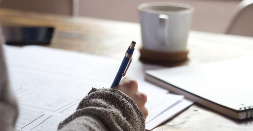 Una mano escribe en un papel frente a un café.