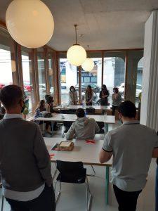 Personas de pie y sentadas en las mesas de la cafetería. Es una cafetería amplia con un gran ventanal que da a la calle.