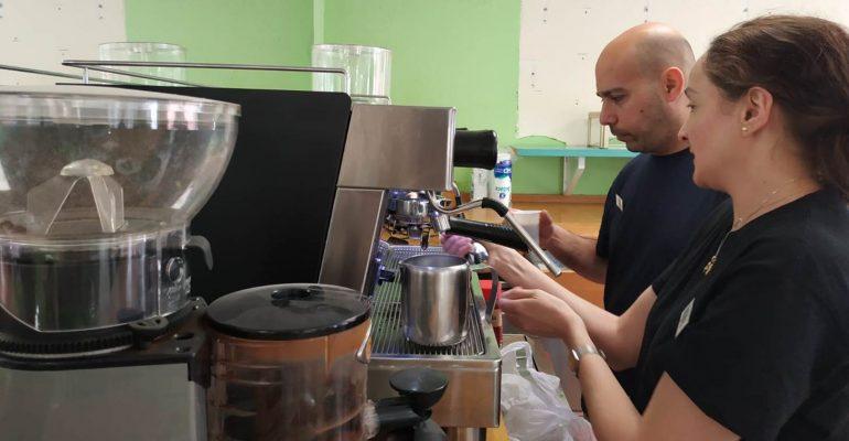 Mujer poniendo una cafetera detrás de la barra