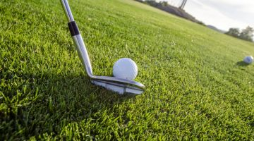 Palo y pelota de golf sobre césped.